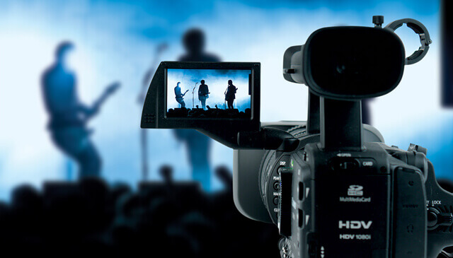 Video camera recording two musicians on stage paying the guitar.