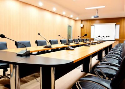 A conference room with a large table with microphones in the middle of the table surrounding by black chairs